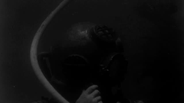 underwater - scuba divers underwater - c.u. a diver adjusting air screw on his helmet - b&w. - undervattensdykning bildbanksvideor och videomaterial från bakom kulisserna