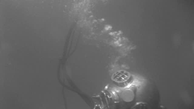 vídeos de stock e filmes b-roll de underwater - scuba divers underwater - c.u. a diver with electric torch walking r to l - b&w. - capacete