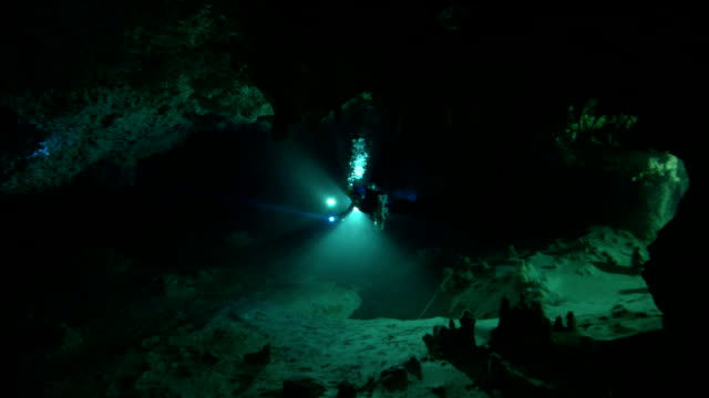 scuba divers use flashlights in an underwater cave. - esplorazione video stock e b–roll