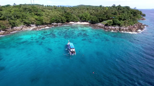 a scuba diving boat mores off a dive site in ko racha island, thailand - david ewing stock-videos und b-roll-filmmaterial