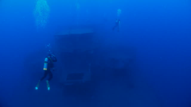 Scuba diving in the shipwreck at deep sea