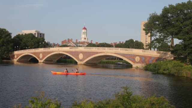 A sculler rows on the Charles River past the Harvard University Campus in Cambridge MA Tuesday June 30 2015 Shots The sunset shines against a bridge...