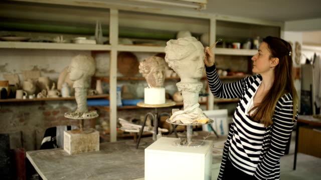 vídeos de stock, filmes e b-roll de artista do sculptor que cria uma escultura do busto com argila. - arcaico