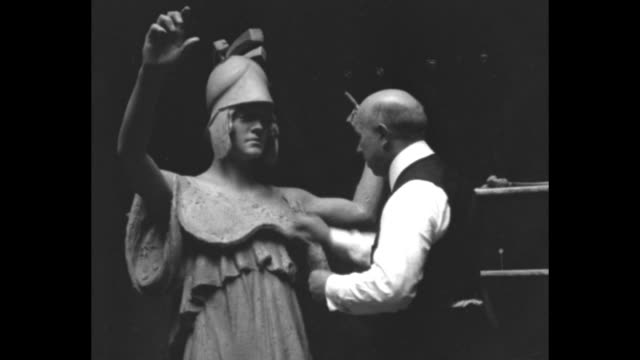 Sculptor Henry Augustus Lukeman works on the figure of Athena the Roman goddess of war as part of the Peace Memorial and he stands at a closed door /...