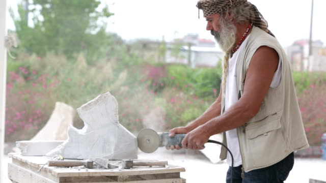 Sculptor is creating a sculpture using a hand tool