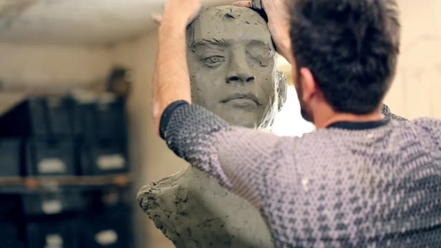 sculptor is working on the creation of a monument - skulptur kunstwerk stock-videos und b-roll-filmmaterial