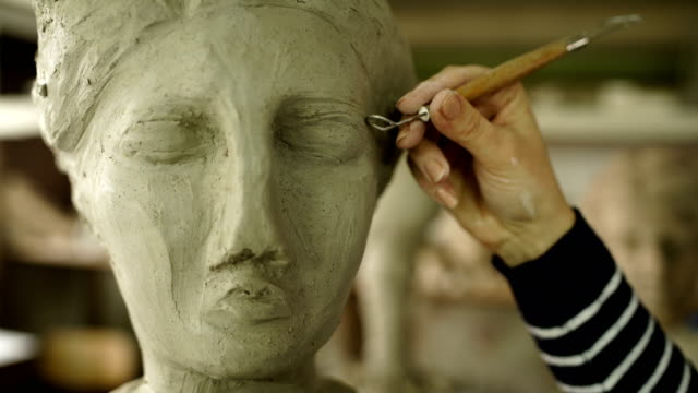 sculptor modelling sculpture adjusting face details - sculpture stock videos & royalty-free footage