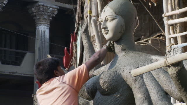 a sculptor slathers clay onto the neck of a statue of kali in calcutta. - menschlicher hals stock-videos und b-roll-filmmaterial
