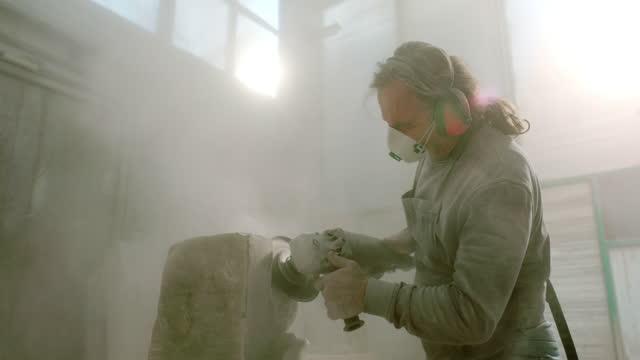 vidéos et rushes de slo mo ld sculpteur lissant la surface de la pierre avec un broyeur d'angle - caillou