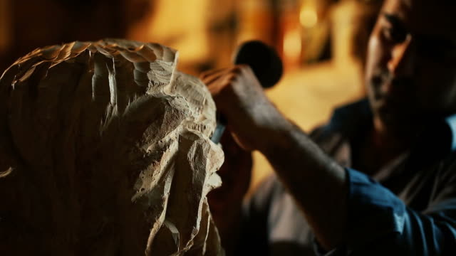 Sculptor working with wooden statue and carving wood