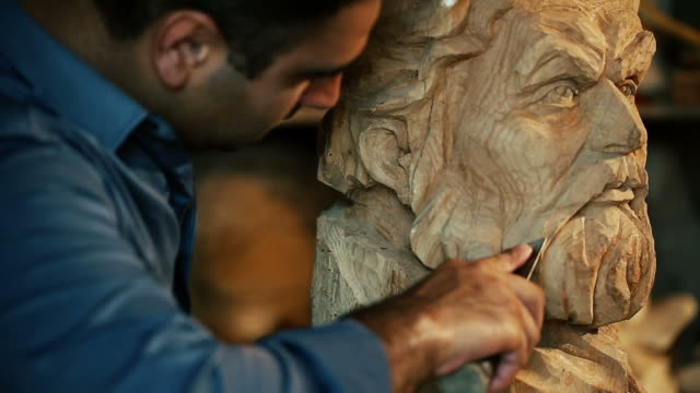 vídeos de stock e filmes b-roll de sculptor working with wooden statue and carving wood - figura masculina