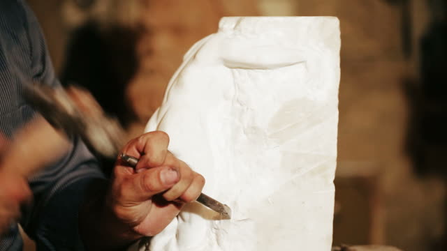 Sculptor works with marble statuette