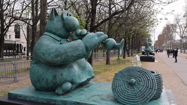 """sculpture depicts """"the cat"""" playing the flute during the inauguration of the exhibition the cat « deambule » by philippe geluck on the... - カトゥーニスト点の映像素材/bロール"""
