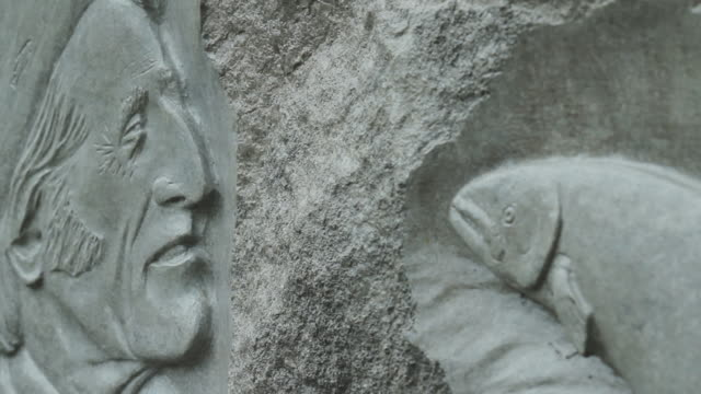 A sculpture of a fisherman and a fish in the rock