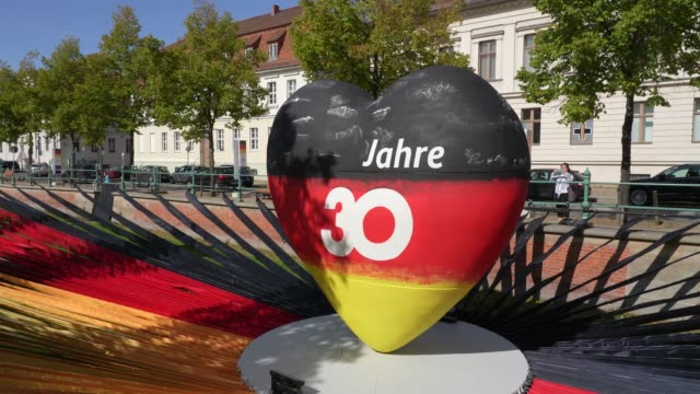 a sculpture of a heart in the colors of the german flag that reads 30 years as part of an outdoor exhibition marking the upcoming 30th anniversary of... - 30 34 years stock videos & royalty-free footage