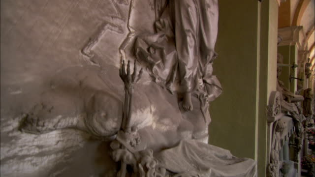 a sculpture of a skeleton fends off an attack from a holy angel in the mausoleum of the monumental cemetery of staglieno. available in hd. - angel stock videos & royalty-free footage