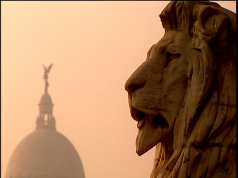 sculpture of imperial lion colonial residence and statue of trumpet player set against soft amber haze of sunrise calcutta - kolkata stock videos & royalty-free footage