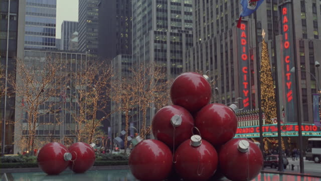 a sculpture of large red christmas ornaments decorate a fountain in front of radio city music hall. - radio city music hall stock videos and b-roll footage