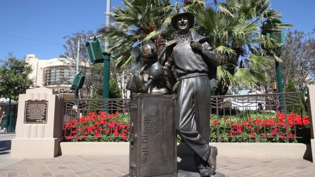 """september 02: sculpture """"storytellers"""" of walt disney next to mickey mouse at disney california adventure park in front of a recreation of the... - storyteller stock videos & royalty-free footage"""