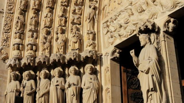 cu tu sculptures in front of cathedral gate  /  paris city, paris, france - figura maschile video stock e b–roll