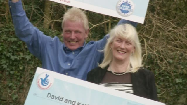 scunthorpe couple win euromillions draw for second time; david long and kathleen long holding two giant cheques for euromillions winnings at photocall - 宝くじ点の映像素材/bロール