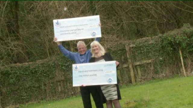 scunthorpe couple win euromillions draw for second time ext david long and kathleen long holding two giant cheques for euromillions winnings - winnings stock videos and b-roll footage