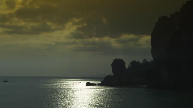 vídeos de stock e filmes b-roll de ws sea and silhouetted cliffs with boats / krabi, thailand - província de krabi