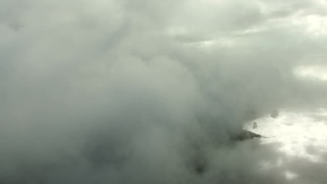 MS AERIAL Sea cliffs covered by clouds and fog / Hawaii, United States