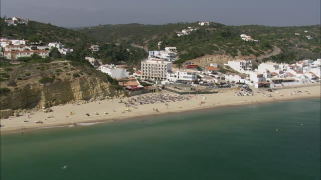 aerial ws sea coast with tourist town / salema, faro, portugal - algarve stock-videos und b-roll-filmmaterial