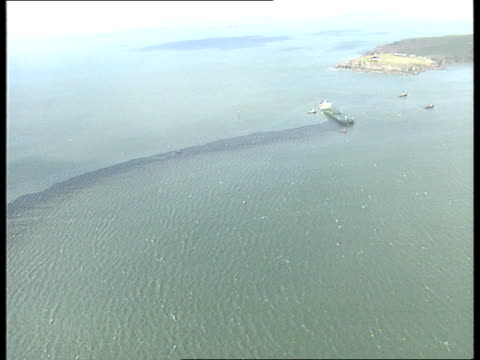 WALES Milford Haven Waves breaking over striken hull of `Sea Empress' tanker oil slick leaking from tanker oil washing up onto shore seabird being...