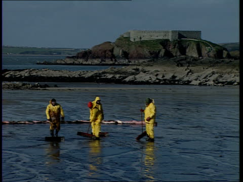 vídeos de stock, filmes e b-roll de sea empress oil tanker shipwreck and clean-up operation; sign 'oil on beach' with workers cleaning up beach in background / firefighter looking on /... - gastrópode