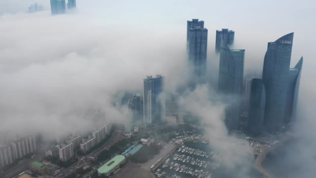 sea fog cityscape around busan yachting center and centum city / busan, south korea - bedeckter himmel stock-videos und b-roll-filmmaterial