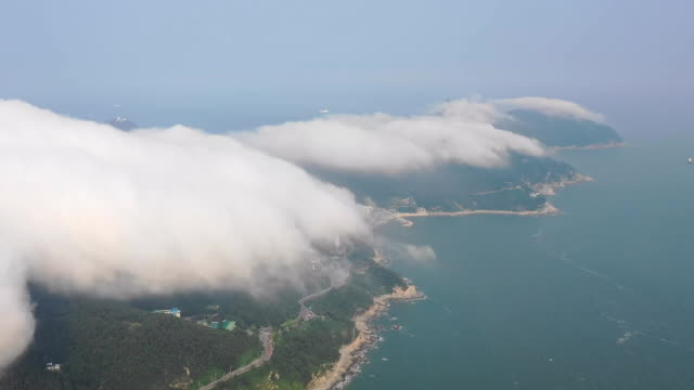 sea fog over bongnaesan mountain and nearby city buildings / yeongdo-gu, busan, south korea - bedeckter himmel stock-videos und b-roll-filmmaterial