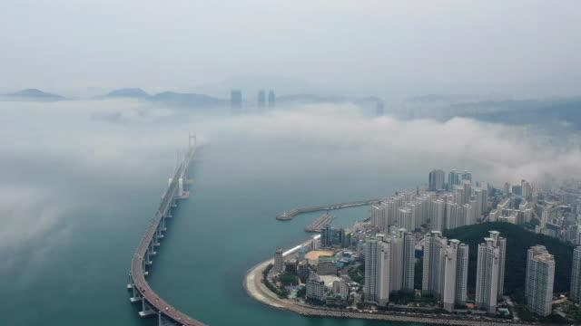 sea fog scenery of gwangandaegyo bridge and nearby city buildings / busan, south korea - waterfront stock videos & royalty-free footage
