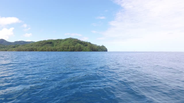 sea in front of mountains covered with tropical forest - huahine island stock videos and b-roll footage