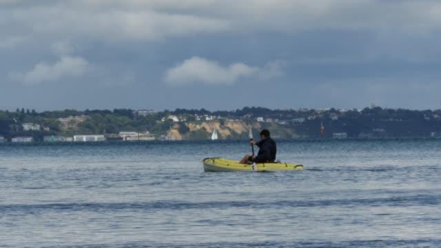 vídeos y material grabado en eventos de stock de sea kayaker paddles out of shot with cliffs in background - studland heath