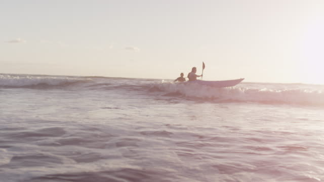sea kayakers ride waves to shore, slow motion - kajak stock-videos und b-roll-filmmaterial
