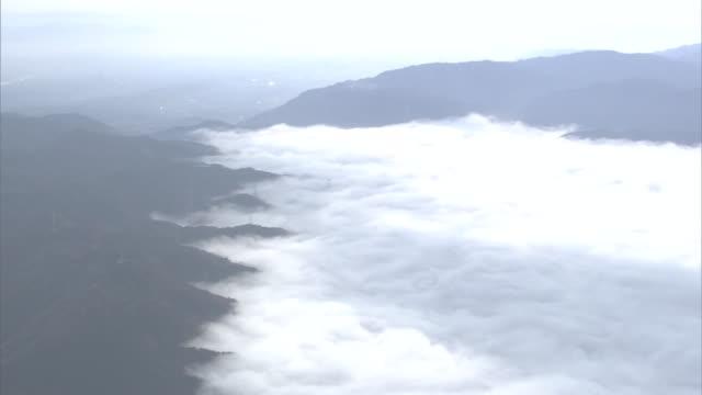 vidéos et rushes de aerial, sea of clouds over the city of kameoka, kyoto, japan - dépression terrestre