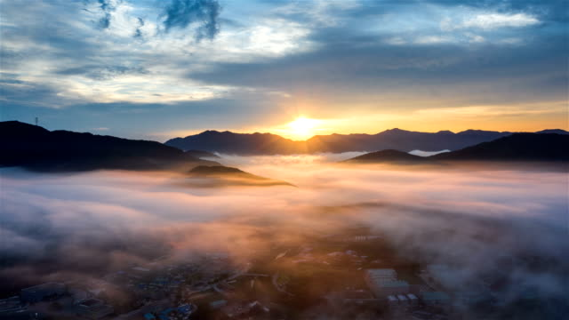 sea of clouds over village in mountain at sunset / gyeonggi-do, south korea - atmosphere filter stock-videos und b-roll-filmmaterial