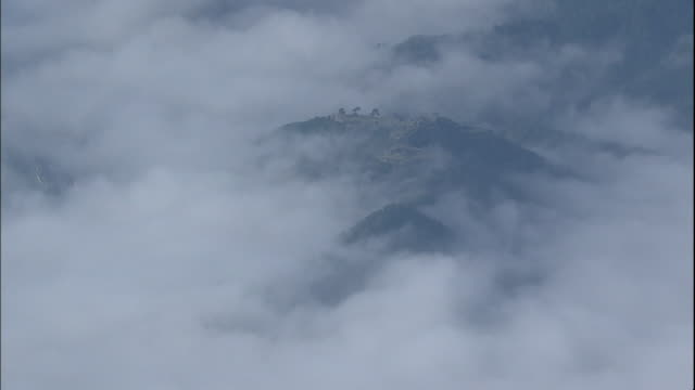 a sea of clouds surround the ruins of takeda castle on a mountaintop in japan. - 遺跡点の映像素材/bロール