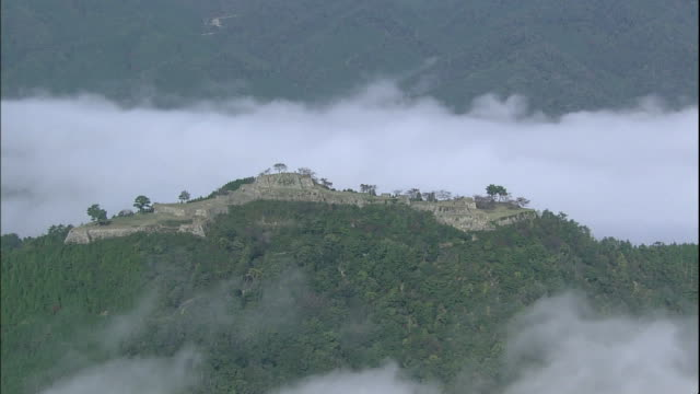 a sea of clouds surrounds the ruins of takeda castle as tourists enjoy a mountain view. - 遺跡点の映像素材/bロール