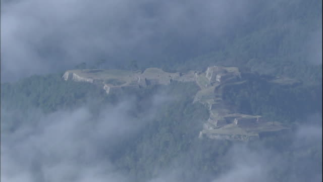 a sea of clouds surrounds the ruins of takeda castle constructed on a mountain in hyogo, japan. - 遺跡点の映像素材/bロール