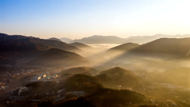 sea of clouds with rays of light on village in mountain / gyeonggi-do, south korea - atmosphere filter stock-videos und b-roll-filmmaterial