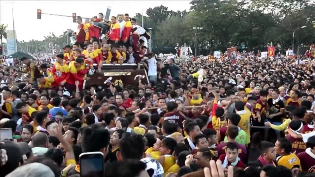 A sea of heaving towel waving humanity swarms a black statue of a cross bearing Jesus Christ in the Philippine capital as the Catholic faithful...