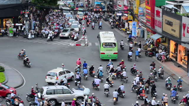 MS Sea of mopeds negotiating round about in central Saigon / Ho Chi Minh City, Saigon, Viet Nam