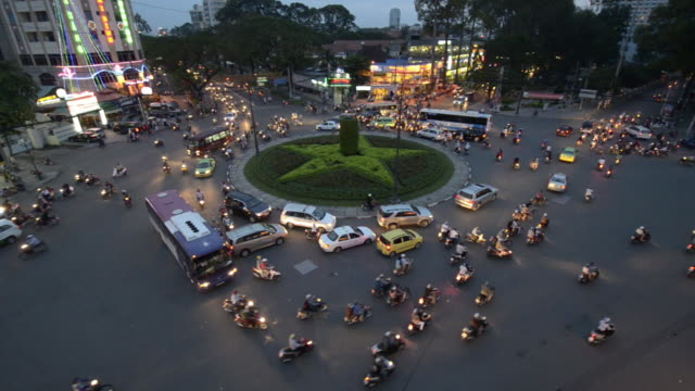 a sea of mopeds negotiating round about in central saigon, ho chi minh, vietnam, asia - sitting点の映像素材/bロール