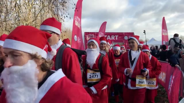 a sea of santa clauses pulled on their running boots and pompom hats for a charity dash in london to raise money for a leading children's hospital... - pom pom stock videos & royalty-free footage