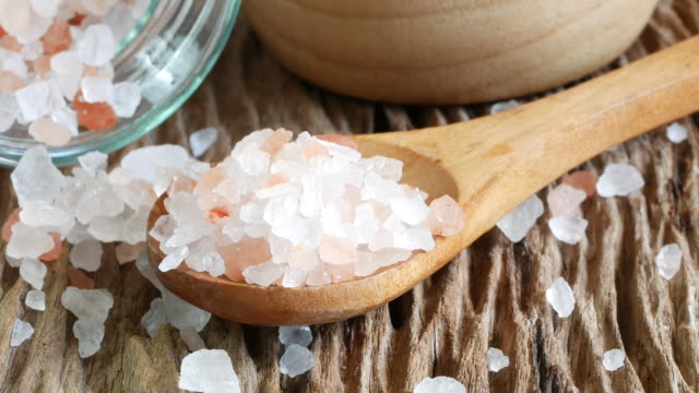 sale marino e himalayano. cristalli di sale sul vecchio tavolo di legno. - sale video stock e b–roll