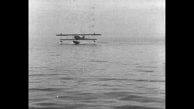 stockvideo's en b-roll-footage met sea sled speeding along surface of water / seaplane flying landing on water being pulled up ramp of floating hangar / shot of hangar - amerikaanse zeemacht