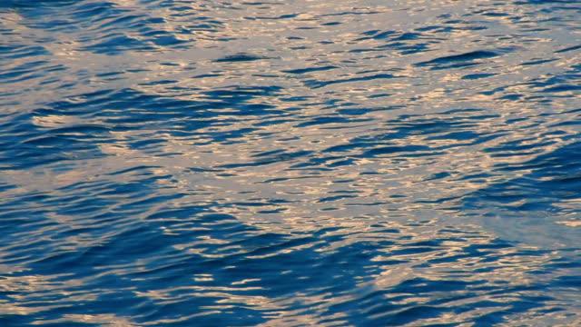 Mar de superficie con reflejos de salida del sol
